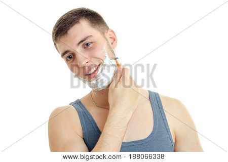 a cheerful young man with foam on his face worth bending head smiling and shaves his beard is isolated on a white background close-up