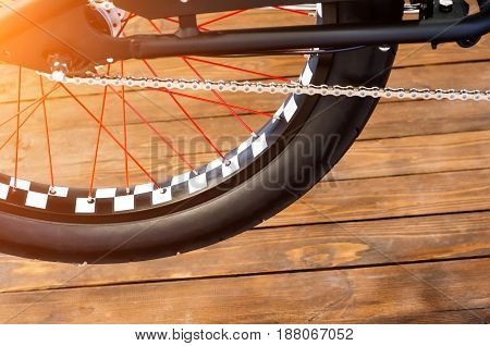 Wheel of a stylish bicycle with a black and white rim and a black rubber tire on a stylish wooden background