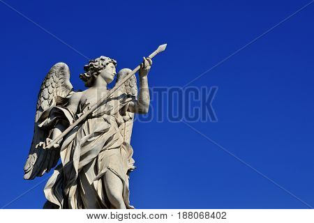 Angel statue holding the Holy Lance of Longinus on Sant'Angelo Bridge in Rome (with blue sky and copy space)