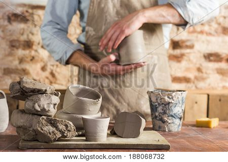 pottery, workshop, ceramics art concept - young craftsman's hands holding unbaked jug, male ceramist stand at workplace and wearing apron, workplace with fireclay and unfinished cups, selective focus