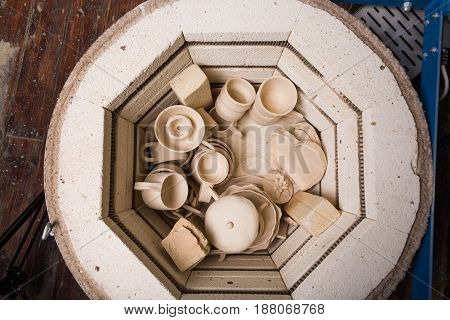 pottery, workshop, ceramics art concept - small electric oven for further roasting of unfinished clay products, kiln for cups and unbaked jugs, flat lay, top view