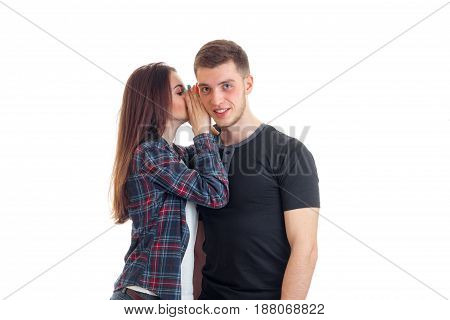 young girl whispering guy in his ear isolated on white background