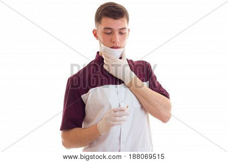 young cute guy doctor in uniforms and gloves isolated on white background