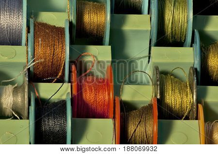 thread on tailor bobbins for sewing machine in box close to