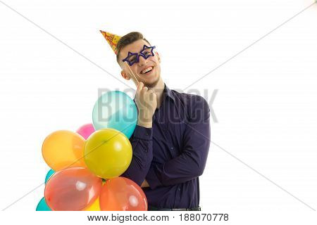 funny guy with balloons in his hands and paper glasses laughs isolated on white background