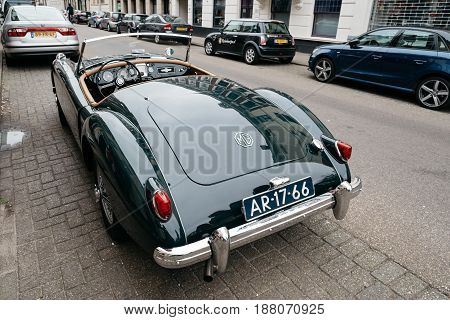 The Hague The Netherlands - August 7 2016: MG vintage green car parked on the street. Rear view. MG Car is a British sports car.