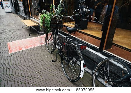 The Hague The Netherlands - August 7 2016: Bicycle parked in a store window of a store in a typical commercial street in the Hague. The Hague is the seat of the Dutch government and multiple international organizations.