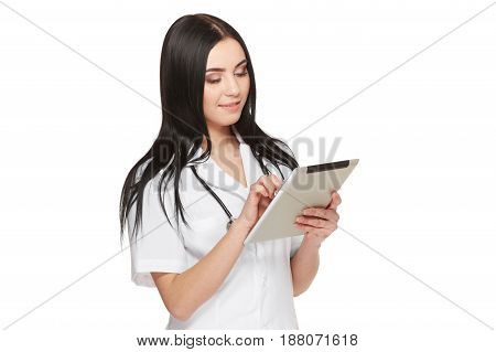 Studio portrait of pretty female assistant of doctor wearing in white uniform with long hair, using tablet and reading information about patient. Nurse at hospital applying new technology in medicine.