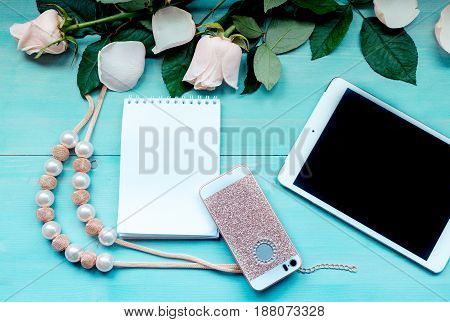 Spring background layout on a blue wooden background with flowers and rose petals Notepad sheets for records of tablet phone and beads accessories