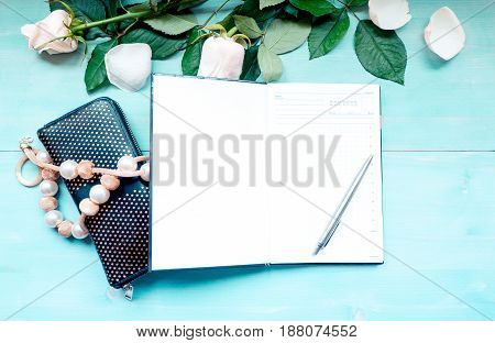 Spring background layout on a blue wooden background with flowers and rose petals daily planner sheets for notes and pen purse and beads accessories