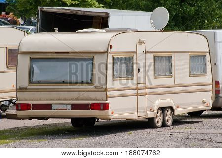 Beige house trailer with an antenna on wheels.