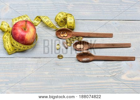 Spoons With Pills Next To Red Apple