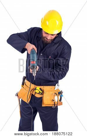 Smiling beard young worker drilling by driller tool and looking down man wearing workswear and belt equipment isolated on white background