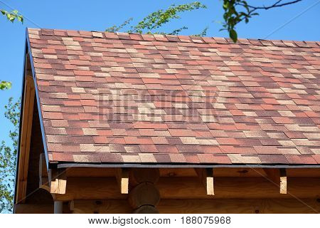 New suburban house from smooth logs and soft motley roof tile in sunny summer day side view closeup
