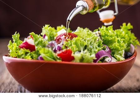 Salad. Vegetable salad. Spring vegetable salad.Fresh vegetable salad with tomatoes onion cheese and olives.Olive oil pouring into bowl of salad.