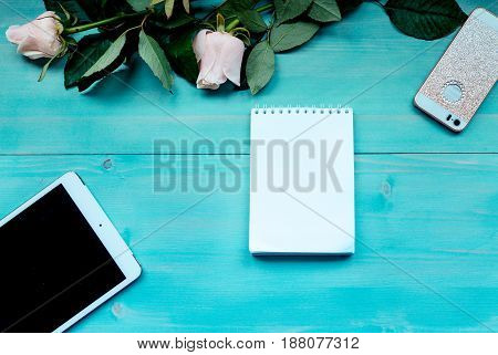Spring wooden background layout blue on blue wooden background with flowers of roses Notepad and sheets for records of phone and tablet