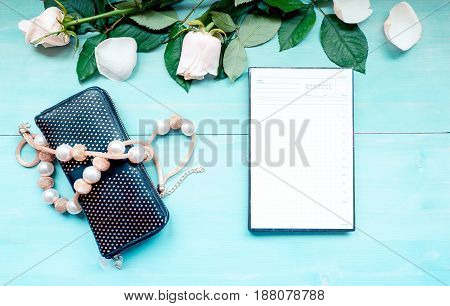 Spring background layout on a blue wooden background with flowers and rose petals daily planner sheets for notes and purse and beads accessories