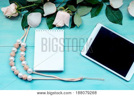 Spring background layout on a blue wooden background with flowers and rose petals Notepad sheets for records of tablet  and beads accessories