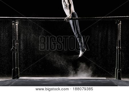 Male athlete performing handstand on gymnastic parallel bars with talcum powder