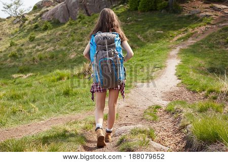 Woman hiker smiling happy  walking with hiking poles.