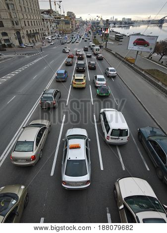 KIEV - UKRAINE - DECEMBER, 2011: View from the bridge to the city traffic along the Dnieper River at Poshtova Square in Kiev. Cars move in dense rows in the evening. Vertical photo, top view.