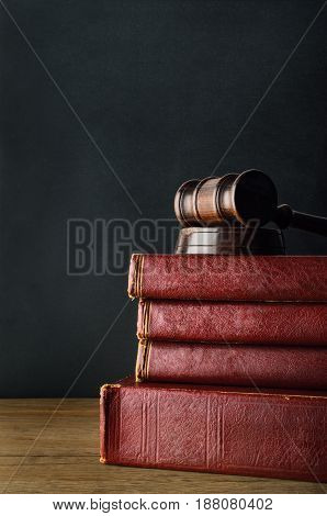 Dark wood gavel on top of a stack of old used books with blank spines on oak desk with black chalkboard background.