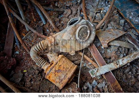 Old rotten Soviet gas mask with rusty filter on rusty metal floor of ship with garbage and scrap