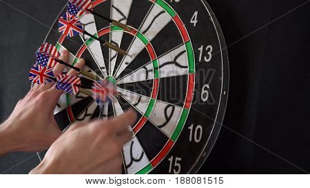The player's hands take out darts from the dartboard.