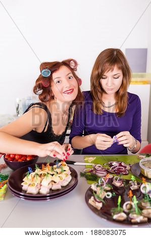 Two young pretty woman housewife cooking with curlers on hair