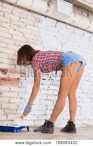 Attractive Woman Paints White Brick Wall Brush