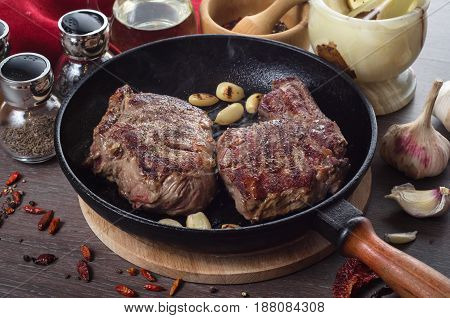 Grilled rib eye steak composition on grill iron pan on a wooden background