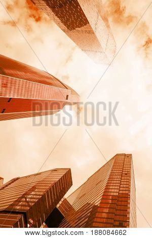 Low angle view of of modern glass reflective office skyscrapers against cloudy sky and sun light. Bright sepia toned image