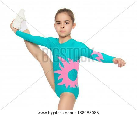 Very flexible little girl gymnast, junior school age, in a beautiful gymnastic swimsuit turquoise.She lifted her foot and took her hand.Isolated on white background.