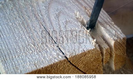 a worker uses a chisel to work with wood Board.