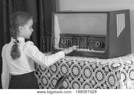 A beautiful little schoolgirl girl in a white blouse and black long skirt, with neatly braided pigtails on her head.She presses the keys of the old radio. Interior of the fifties of the last century.