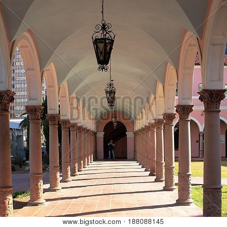 Archway of the Old Pima County Courthouse in Tucson, Arizona, a tourist is taking pictures.