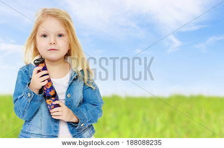 Little girl with blond loose hair, in a denim jacket holding in his hand a telescope. Close-up.On the background of green grass and blue sky with clouds.