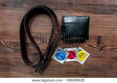 male contraception for safe sex with condoms and wallet on wooden desk background top view