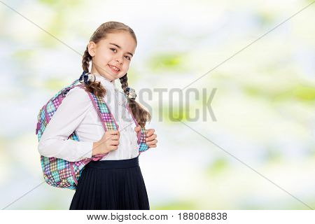 Beautiful little blond schoolgirl, with long neatly braided pigtails. In a white blouse and a long dark skirt.She wears a school satchel.Summer white green blurred background.