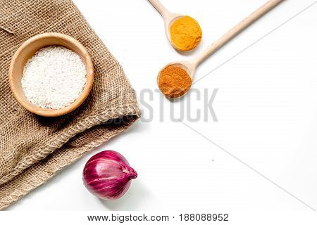 cooking paella with rice ingredients on white kitchen desk background top view mockup