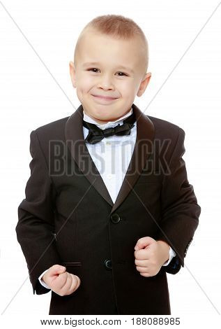Beautiful little blond boy in a fashionable black suit with a tie.The boy tightly clenched his fists.Isolated on white background.