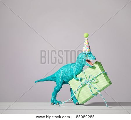 Dinosaur toy with party hat holding a birthday present.