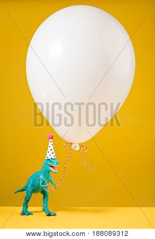 Dinosaur toy with birthday hat holding a white balloon on a yellow background.