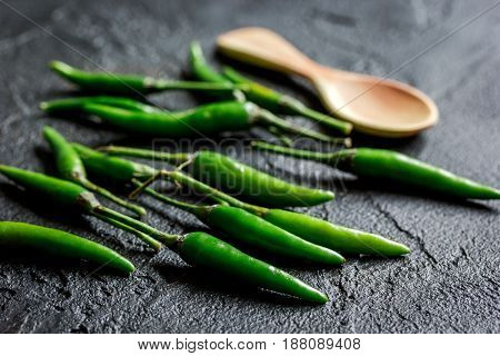 cooking hot sauce with green chili pepper on dark kitchen table background close up
