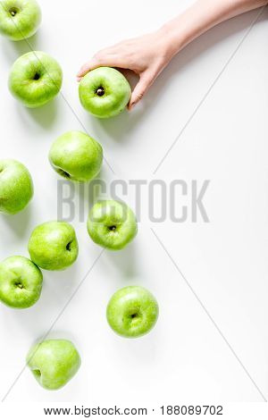natural food design with green apples in hands on white desk background top view