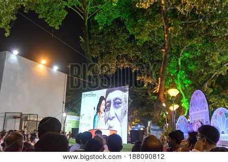 KOLKATA WEST BENGAL INDIA - 9TH MAY 2017 : Female announcer seen in a giant screen amongst audience at Rabindra Jayanti celebration (birthday of Late Nobel winner Poet Rabindranath Tagore). Bengalis favourite poet.