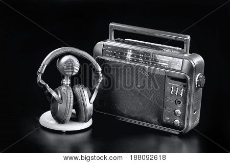 Old time radio with mic and headphones in black and white.