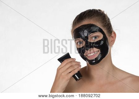 Happy beautiful girl with acne smiling on a white background in a cosmetic mask black