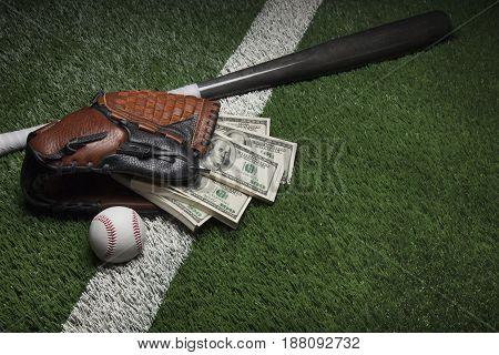 A baseball mitt full of hundred dollar bills on a field with a bat and ball