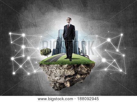 Elegant businessman on flying green island against concrete background
